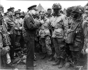 Black and white photo in which General Dwight D. Eisenhower addresses American paratroopers prior to D-Day.